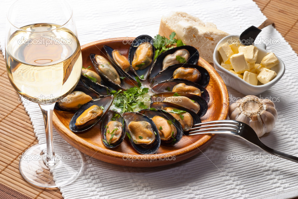 Mussels in garlic butter sauce in round wooden plate — Stock Photo #6767043