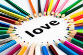 Many colored pencils arranged in circle on the word love — Stock Photo