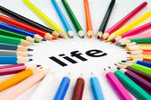 Many colored pencils arranged in circle on the word life — Stock Photo