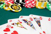 Poker, royal flush and unfocused gambling chips — Stock Photo