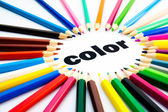 Many colored pencils arranged in circle on the word color — Stock Photo