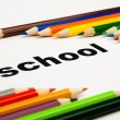 Many colored pencils arranged around the word school — Stock Photo