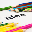 Many colored pencils arranged around the word idea — Stock Photo