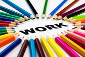 Many colored pencils arranged in circle on the word work — Stock Photo