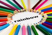 Many colored pencils arranged in circle on the word rainbow — Stock Photo