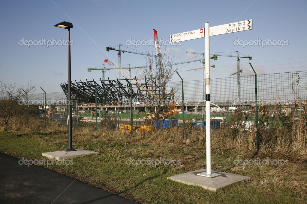 The London Olympic Stadium under construction behind pedestrian signs. — Stock Photo #6830702