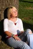 Blond Woman Sitting And Sunning Herself By Tree — Stock Photo