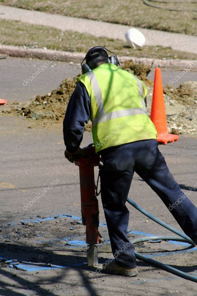 Back view of a worker using a jackhammer on asphalt at a road construction site. — Stock Photo #6847011