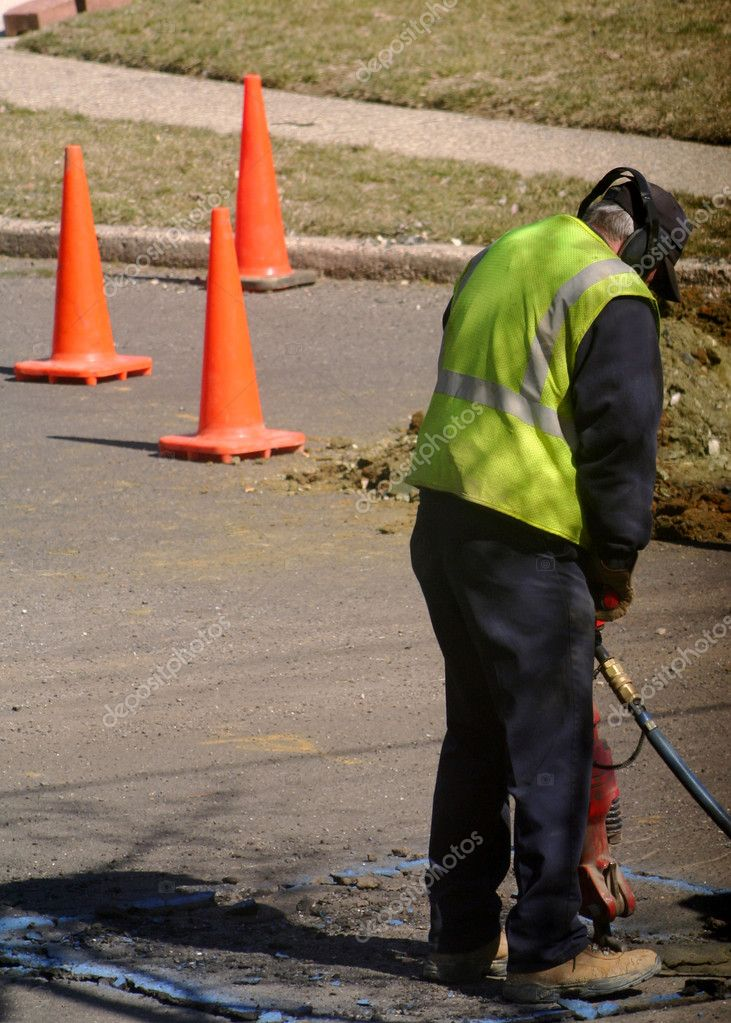 Worker using a jackhammer on asphalt at a road construction site. — Stock Photo #6847127