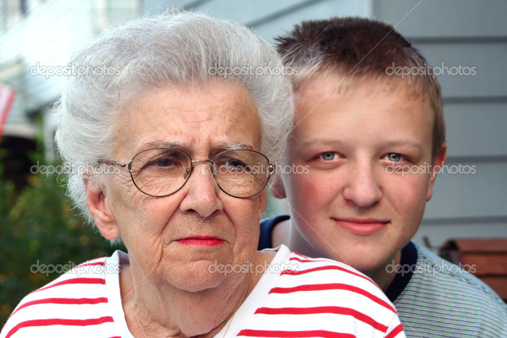 Head and shoulders shot of a senior citizen woman with her teenage grandson looking over her shoulder, taken outdoors.  Stock Photo #6847271