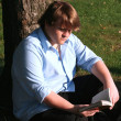 Stock Photo: Teen Boy Reading In Park
