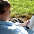 Teen Engrossed In Book Outdoors — Stock Photo
