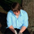 Stock Photo: Teen By Tree Reading
