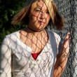 Young Blond Woman Covered by Fence Shadows — Stock Photo