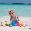 A baby girl is playing with her toys on the beach — Stock Photo #7236287