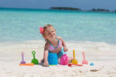 A baby girl is playing with her toys on the beach — Stock Photo