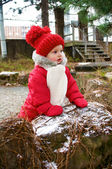 Adorable baby girl in red snowsuit — Stock Photo