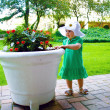 A baby girl and a flower pot — Stock Photo