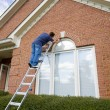 Painter painting trim around doors windows - Stock Photo