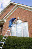 Painter painting trim around doors windows — Stock Photo