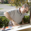 Carpenter repairing window frame — Stock Photo