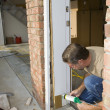 Carpenter caulking door casing — Stockfoto