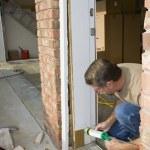 Carpenter caulking door casing — Stock Photo #6769373