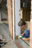 Carpenter caulking door casing — Stock Photo