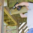 Stock Photo: Carpenter securing deck