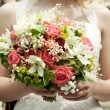 Bride holding bunch of flowers at wedding — Stock Photo