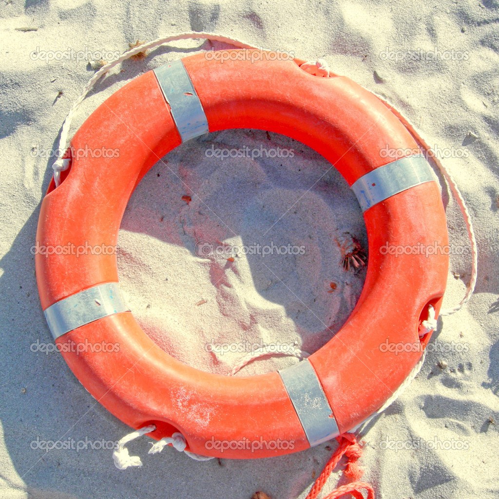 Orange life buoy over sand on the shore  Stock Photo #6866835