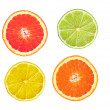 tranches de pamplemousse rose, citron vert, citron et orange isolé sur blanc — Photo