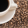 Stock Photo: Freshly brewed coffee in white cup over dark roasted coffee bean