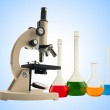 Laboratory metal microscope and test tubes with liquid over blue — Stock Photo