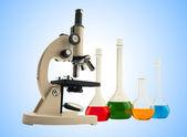 Laboratorio metallo microscopio e provette con liquido sul blu — Foto Stock