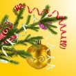Christmas balls hanging with ribbons on fir tree over yellow — Stock Photo