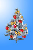 Decorated christmas tree over blue background — Stock Photo
