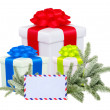 Foto Stock: Christmas gifts with post card and branch firtree isolated on wh