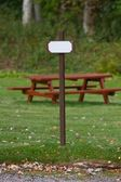 Signpost beside park bench — Stock Photo