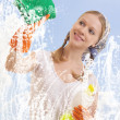 Stock Photo: Young woman washing window