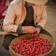 Foto de Stock  : Asian man in a Chinese hat with a basket of small red apples