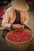 Asian man in a Chinese hat with a basket of small red apples — Stockfoto