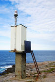 A small lighthouse with solar battery on the rock. — Stock Photo