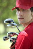 Golfer holding golf clubs. — Stock Photo