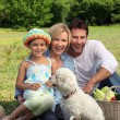 Parents and young daughter with dog and basket of vegetables — Stock Photo