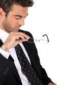 Businessman taking off his glasses — Stock Photo