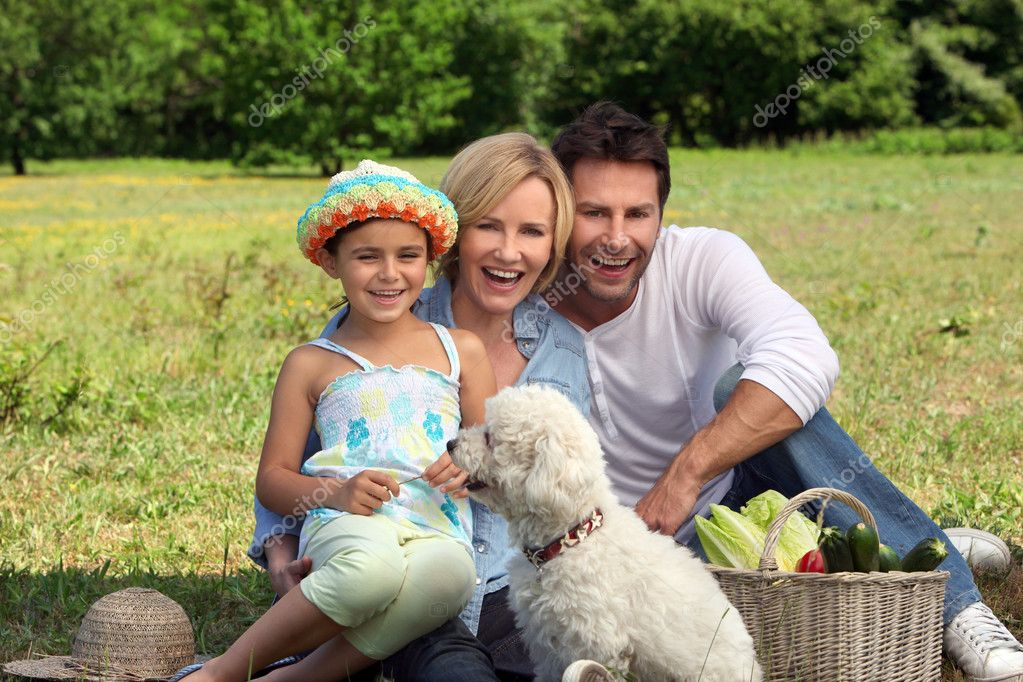 Parents and young daughter with dog and basket of vegetables — Stock Photo #7026355