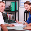 Tradeswoman and an engineer discussing a blueprint — Stock Photo