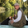 Hunter with a shotgun and dog on a boat — Stock Photo #7089714