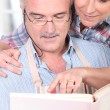 Mature couple consulting cookbook — Stock Photo